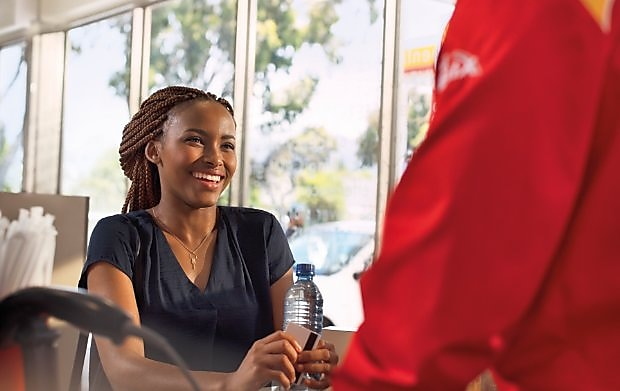 Female customer smiling at a Shell retail station.
