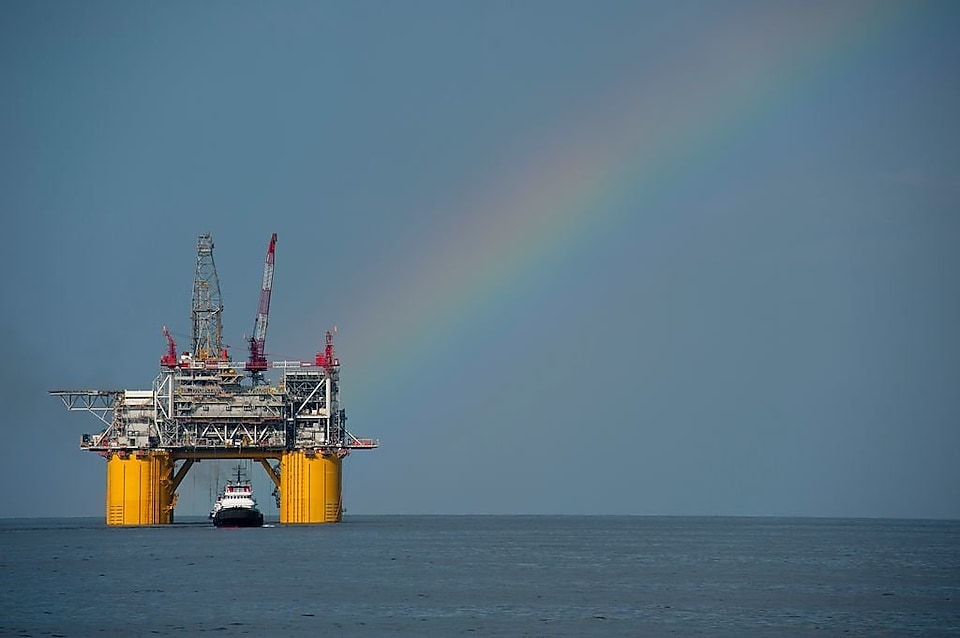 A Shell offshore rig with a rainbow in the background.