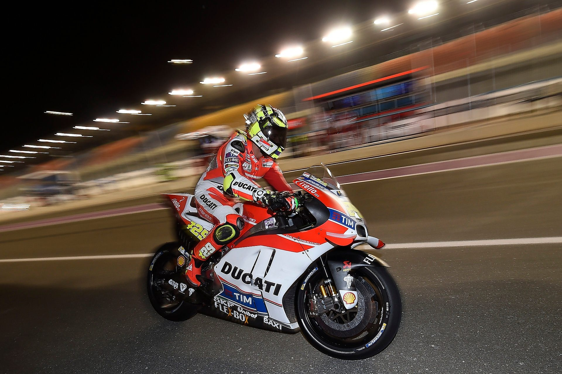 Ducati rider riding motorcycle at high speed on a track at night