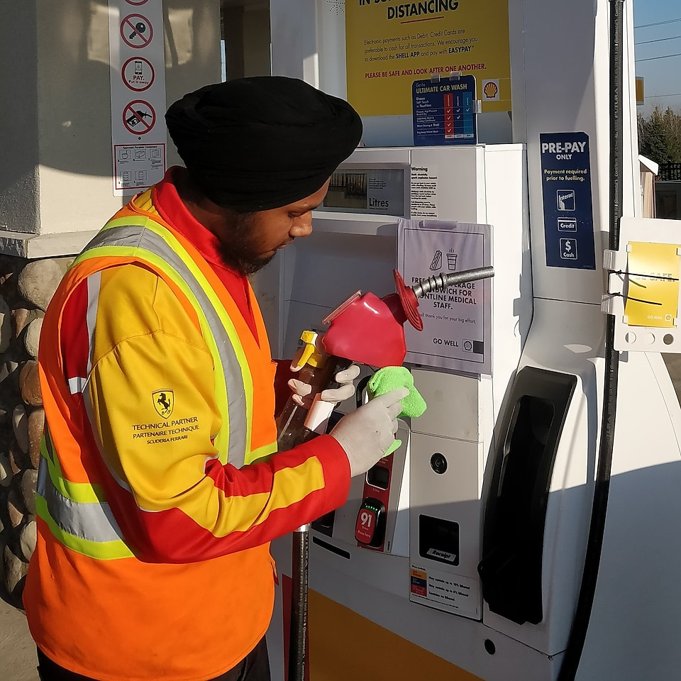 A Shell retail employee wipes the handle of a fuel pump nozzle.