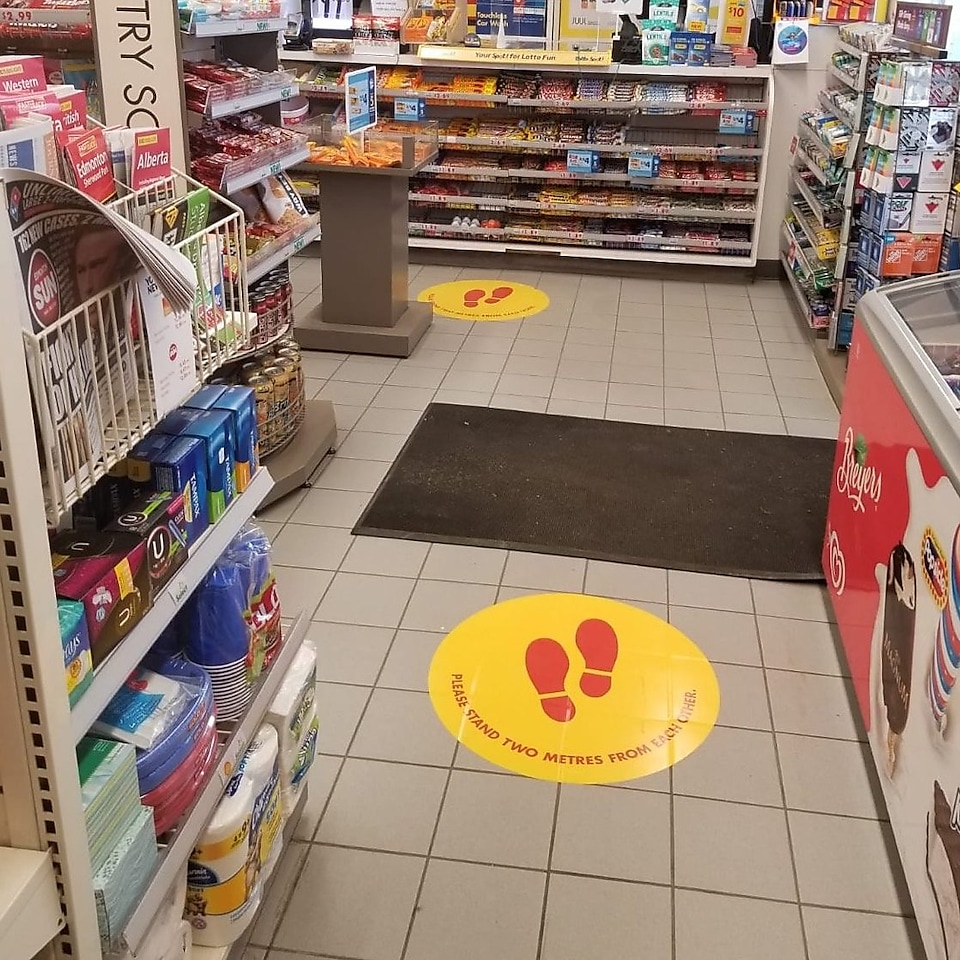 Round yellow floor decals inside a Shell retail store indicate social distancing measures.