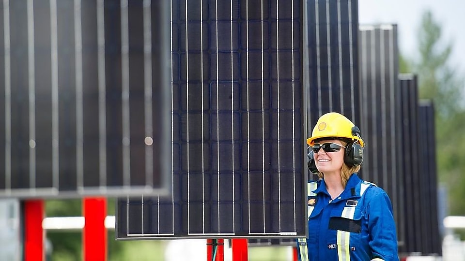 An employee inspects the solar panels at a well site in the Groundbirch field.